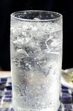 Sparkling Water. A frosty drink of sparkling water in a glass mug with a straw Stock Photos