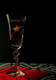 Sparkling water with fruit in a glass. Sparkling water with raspberries, blueberries and grapes in a high glass on red serwetve and black background. Clearly Stock Image
