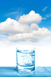 Sparkling water glass on blue sky Fresh cold drink Royalty Free Stock Images