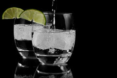 Sparkling water on ice. Two glasses of sparkling water on ice with lime slices stock images