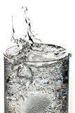 Sparkling water with ice. Cube of ice dropped into the glass of sparkling water Royalty Free Stock Images