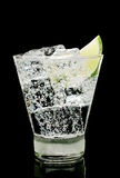 Sparkling water with ice cubes and piece of lime. In old fashion glass on a black background Stock Photos