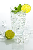 Sparkling water with ice cubes on white background Royalty Free Stock Photo