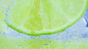 Sparkling water with ice and slices lime on white background stock video