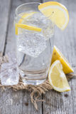 Sparkling Water with Lemon. And ice on wooden background Stock Image