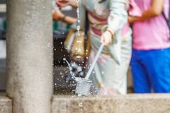 Sparkling water purification at entrance of Japanese temple. Woman in traditional dressing takes water for purification at the entrance of Japanese temple with Royalty Free Stock Photo
