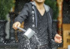 Sparkling water purification at Japanese temple. Man takes water for purification at the entrance of Japanese temple under water stream, Kyoto Stock Photography