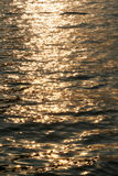 Sparkling water or sea surface. With golden glow royalty free stock photo