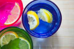 Sparkling water, soda or a gin and tonic in colorful glasses with lemon and ice Royalty Free Stock Photos