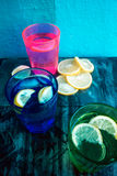 Sparkling water, soda or a gin and tonic in colorful glasses with lemon and ice. Royalty Free Stock Photography