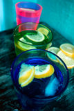 Sparkling water, soda or a gin and tonic in colorful glasses with lemon and ice. Stock Photos
