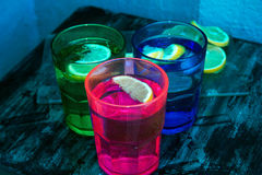 Sparkling water, soda or a gin and tonic in colorful glasses with lemon and ice. Stock Photography