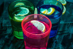 Sparkling water, soda or a gin and tonic in colorful glasses with lemon and ice. Royalty Free Stock Photos