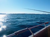 Sparkling water surface and moving fishing rod Royalty Free Stock Images