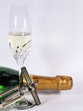 Sparkling wine. A bottle and a glass of sparkling wine with an opener Stock Image