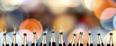 Sparkling wine bottles - colorful panorama. Splashing champagne bottles in front of a colorful blurred background Royalty Free Stock Photography