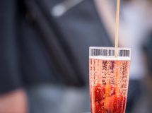 Sparkling wine with fresh strawberries and a straw. royalty free stock photography