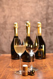 Sparkling wine. A full glass of sparkling white wine and an empty one,two corks on a wooden table and four full bottles on the background Royalty Free Stock Images