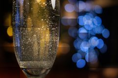 Sparkling wine glass and blurred garland geometry background royalty free stock image