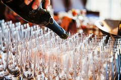 Sparkling wine is poured into glasses. The sparkling wine is poured into glasses royalty free stock image