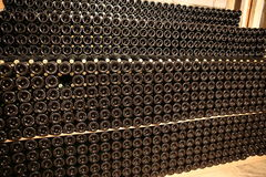 Sparkling wine resting on lees. Large pile of sparkling wine bottles resting on lees in winery cellar with one bottle missing Royalty Free Stock Photos