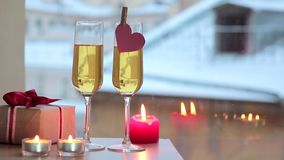Sparkling wine in two glasses and gift for Valentine's Day. View of the snowy roofs stock footage