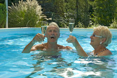 Sparkling wine in water. Happy elderly couple having fun while drinking sparkling wine in blue water pool on on a beautiful day in summer stock photo
