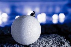 Sparkly конец шарика белого рождества вверх в голубом свете Стоковое Изображение