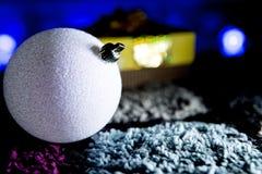 Sparkly шарик белого рождества с подарком в красочной предпосылке Стоковая Фотография