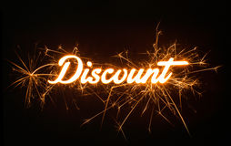Sparkly DISCOUNT word on dark background. Stock Photos