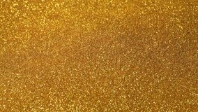 Sparkly Gold Powder Pours Onto Gold Surface