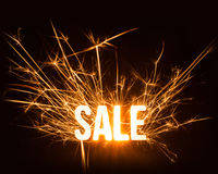 Sparkly Sale word on dark background. Stock Photos