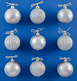 Sparkly Silver Ornaments on Vibrant Blue Background Royalty Free Stock Image