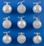 Sparkly silverprydnader på vibrerande blå bakgrund Royaltyfri Bild