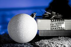 White Christmas Ball with Gift in Blue Backlight. Sparkly White Christmas Ball with Gift in Blue Backlight Royalty Free Stock Image