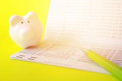 Sparkontobankbok, spargris och penna på gul bakgrund royaltyfri foto