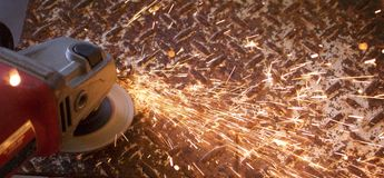 Sparks from and angle grinder on diamond plate steel. Background Royalty Free Stock Images