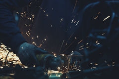 Sparks and angle grinder with sparks around it used to cut steel  pipe in a dark workshop Royalty Free Stock Image