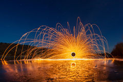 Sparks from the burning steel wool against the starry sky and the frozen river stock photo