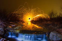 Sparks from the burning steel wool and a waterfall Stock Photography