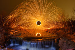 Sparks from the burning steel wool and a waterfall Royalty Free Stock Photo