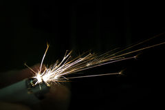 Sparks coming from lighter over black background Stock Photo