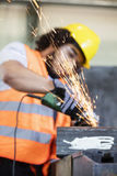 Sparks coming out from grinder with worker in background at metal industry.  Stock Photography