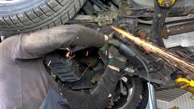 Sparks coming from steel grinder. male worker cutting rusty car parts.