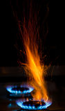 Sparks and flames. Above gas stove burning with blue flames Stock Photos