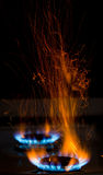 Sparks and flames. Above gas stove burning with blue flames Stock Photo