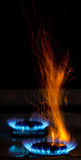 Sparks and flames. Above gas stove burning with blue flames Royalty Free Stock Photos