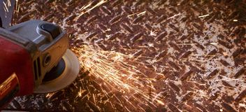 Sparks fly from and angle grinder on diamond plate. Steel Royalty Free Stock Photos