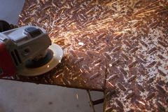 Sparks fly from and angle grinder on diamond plate. Steel Stock Photo