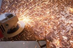 Sparks fly from and angle grinder on diamond plate. Sparks fly from and angle grinder on rusty diamond plate steel Royalty Free Stock Image
